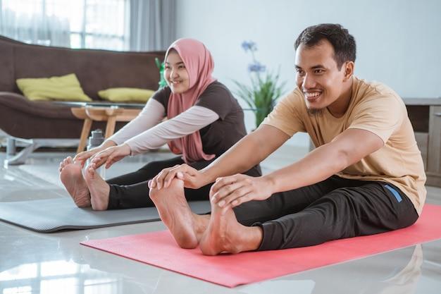 Gelukkig moslim aziatisch geschiktheidspaar, man en vrouw die samen thuis uitoefenen