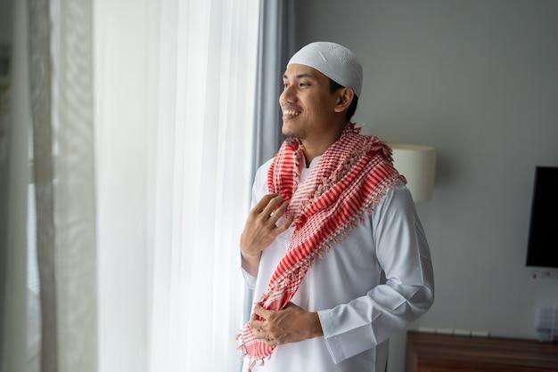Gelukkig moslim aziatische man die zich in de buurt van raam kleedt voordat hij naar de moskee gaat