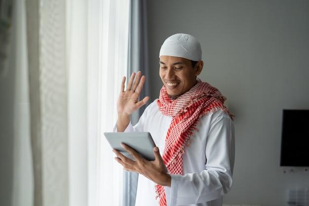 Gelukkig moslim zakenman glimlachen tijdens het gebruik van tablet-pc in de buurt van venster
