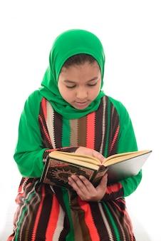 Gelukkig moslimmeisje dat koran leest