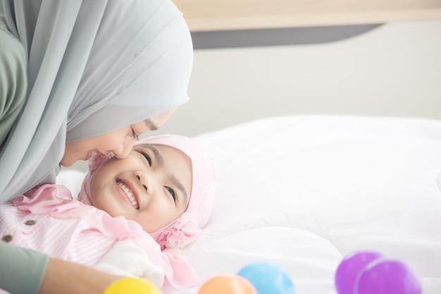 Gelukkig moslimmoeder knuffelen met haar dochter op het bed