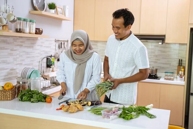 Gelukkig moslimpaar dat samen in de keuken kookt. man en vrouw bereiden zich voor op het avondeten