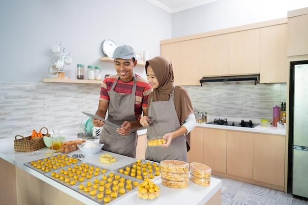 Gelukkig moslimpaar die met tabletpc een cake bakken
