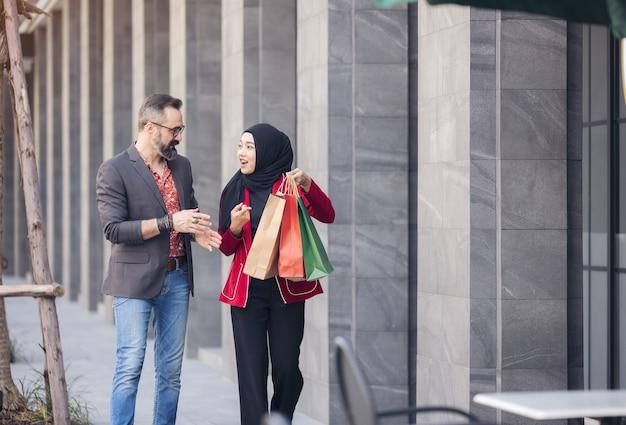 Gelukkig moslimvrouw en jongen vriend met stad winkelen hand met papieren zakken