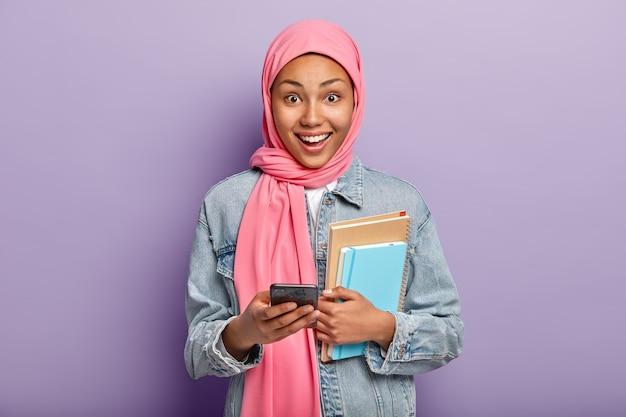 Gelukkig moslimvrouw geavanceerde gebruiker van technologie houdt blocnotes en mobiele telefoon, draagt een roze sluier op het hoofd
