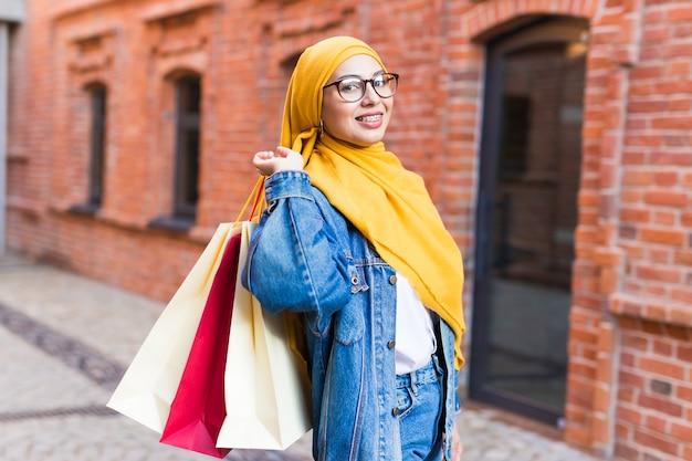Gelukkig moslimvrouw met boodschappentassen na winkelcentrum