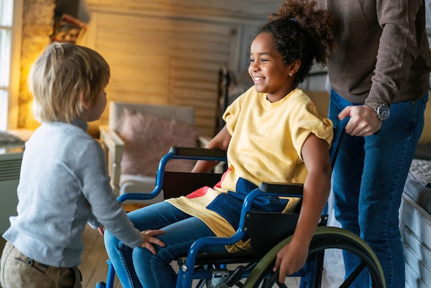Gelukkig multi-etnisch liefhebbend gezin. glimlachend meisje met handicap in rolstoel thuis