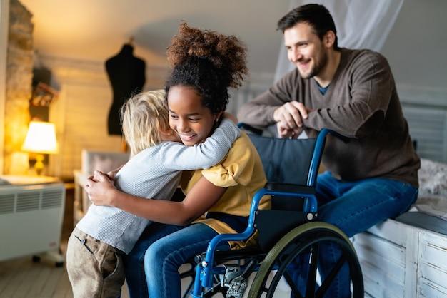 Gelukkig multi-etnisch liefhebbend gezin. glimlachend meisje met handicap in rolstoel
