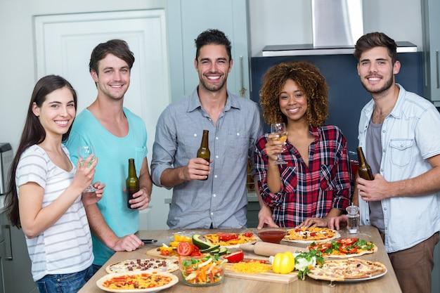 Gelukkig multi-etnische genieten van alcohol en pizza aan tafel