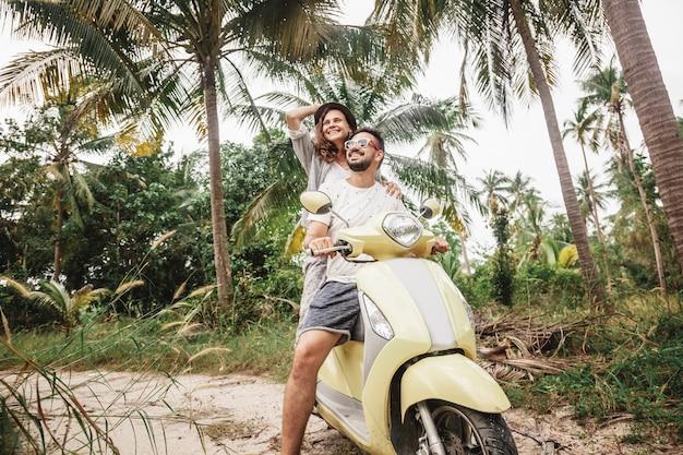 Gelukkig multinationaal paar reizen op een motor in de jungle, huwelijksreis, vakantie,