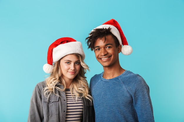 Gelukkig multiraciaal jong paar dat kerstmis rode hoed draagt die over blauwe muur wordt geïsoleerd