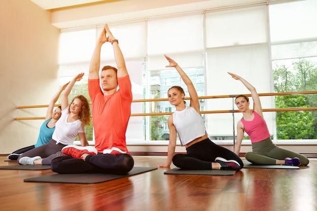 Gelukkig multiraciale groep jonge, lachende mooie meisjes en ruiten in sportkleding, doen yoga-oefeningen in de lotushouding. yogales of fitness. groep fitness concept, groepstrainingen, motivatie.