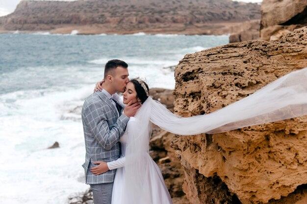 Gelukkig net getrouwd jong stel dat viert en plezier heeft op een rots aan zee, cyprus