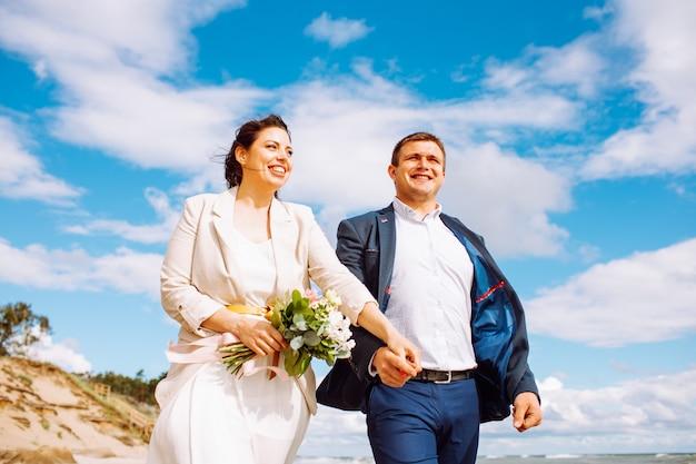 Gelukkig net getrouwd paar van middelbare leeftijd lopen op het strand en hebben plezier op zomerdag.