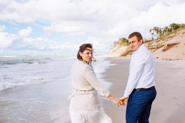 Gelukkig net getrouwd paar van middelbare leeftijd lopen op het strand tegen de blauwe hemel met clouns en hebben plezier op zomerdag.