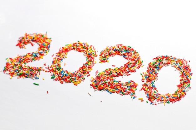 Gelukkig nieuw jaar 2020. de kleurrijke aantalvorm met heldere regenboogsuiker bestrooit geïsoleerd op wit