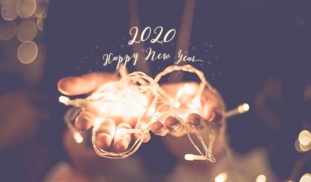 Gelukkig nieuw jaar 2020 gloeiend woord over hand met partij licht koord bokeh