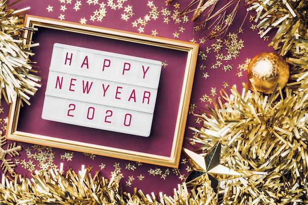 Gelukkig nieuw jaar 2020 lichtvak op purpere lijst. bovenaanzicht van klatergoud, bal, ornament partij versieren op tafel