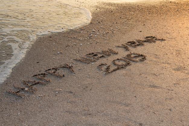 Gelukkig nieuwjaar 2019, geschreven in zand schrijven op tropisch strand met golf