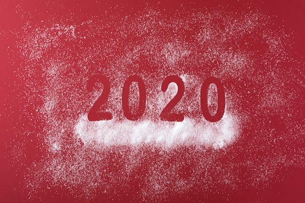 Gelukkig nieuwjaar 2020-datum met sneeuwval op rood