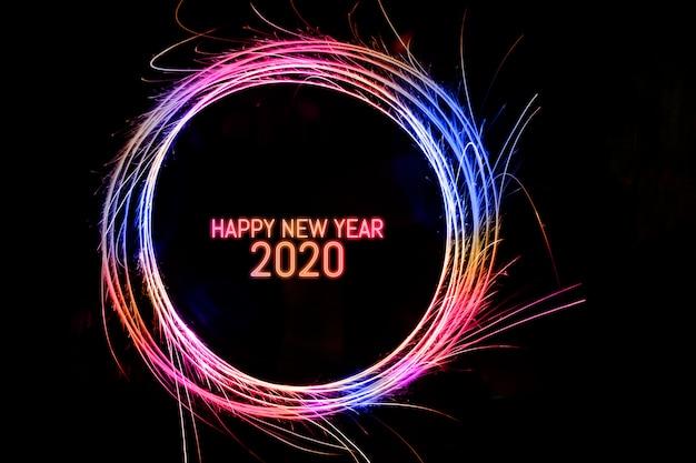 Gelukkig nieuwjaar 2020: geschreven in fonkelende cirkel op zwarte achtergrond
