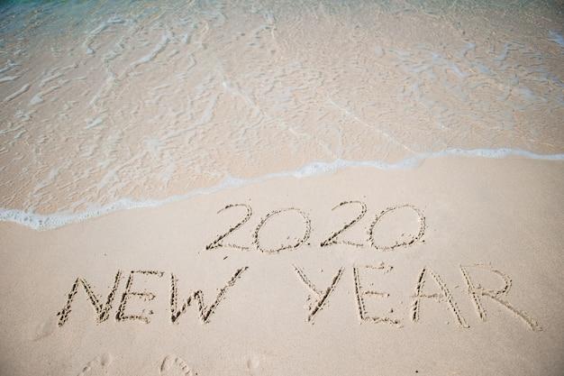 Gelukkig nieuwjaar 2020 geschreven in het witte zand