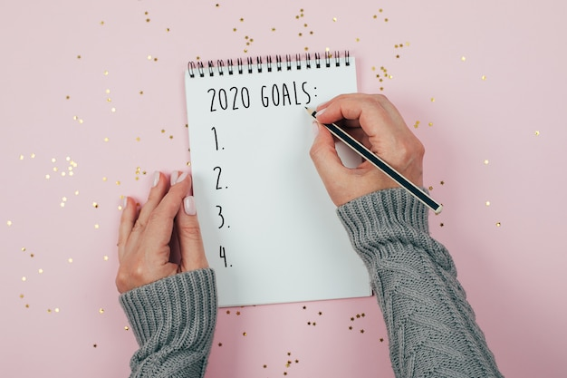 Gelukkig nieuwjaar 2020. hand van de vrouw schrijven 2020 doelen laptop ingericht