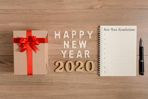 Gelukkig nieuwjaar 2020 hout en nieuwjaarsresolutielijst geschreven