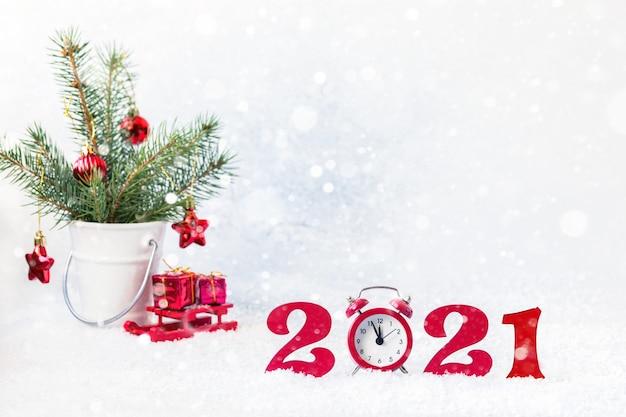 Gelukkig nieuwjaar 2021. 2021 rode cijfers met klok, takken in een emmer en rode geschenken