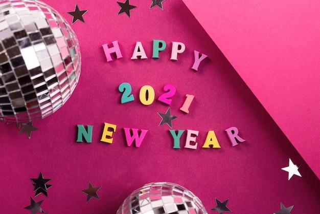 Gelukkig nieuwjaar 2021 begroetingswoorden gemaakt van houten letters, versierd met fonkelende sterren