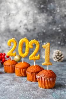 Gelukkig nieuwjaar 2021, cupcakes met gouden kaarsen.