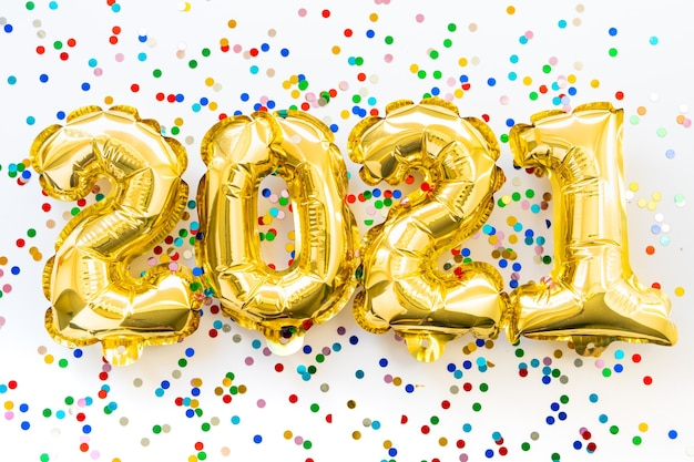 Gelukkig nieuwjaar 2021 feest. goudfolie ballonnen cijfer 2021 en confetti op witte achtergrond