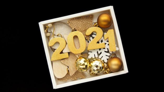 Gelukkig nieuwjaar 2021. gouden cijfers 2021 met gouden kerstballen in zwarte doos