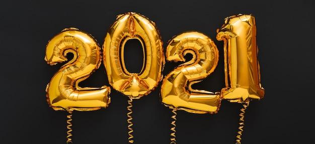 Gelukkig nieuwjaar 2021 gouden luchtballonstekst met linten op zwarte lange banner.