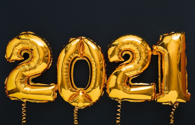 Gelukkig nieuwjaar 2021 gouden luchtballontekst met linten op zwart.