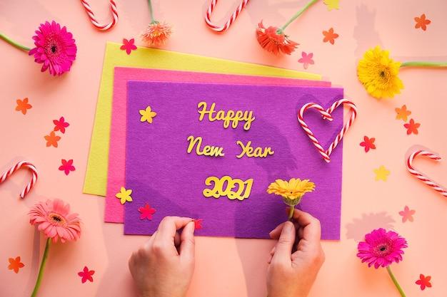 Gelukkig nieuwjaar 2021 in juli levendige plat leggen met gerbera madeliefjebloemen en vilt met papieren tekst.
