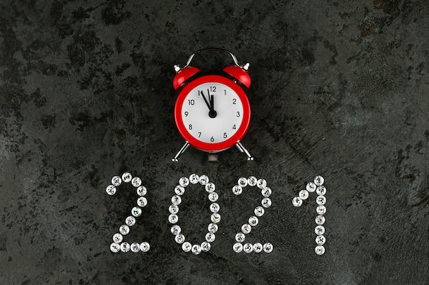 Gelukkig nieuwjaar 2021 met wekker op concrete achtergrond.
