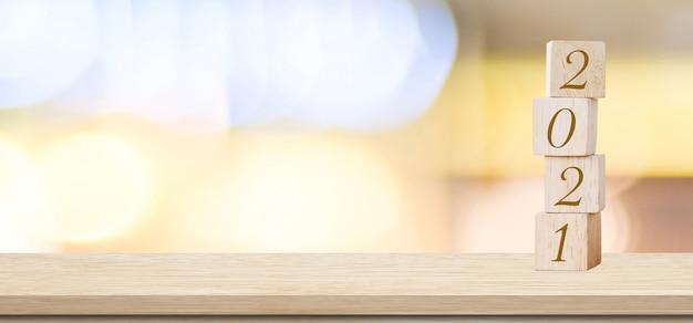 Gelukkig nieuwjaar 2021 op houten kubusblok en abstracte bokeh lichte achtergrond wazig