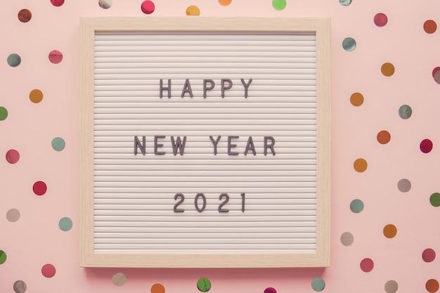 Gelukkig nieuwjaar 2021 op letterbord met kleurrijke stip roze pastel achtergrond