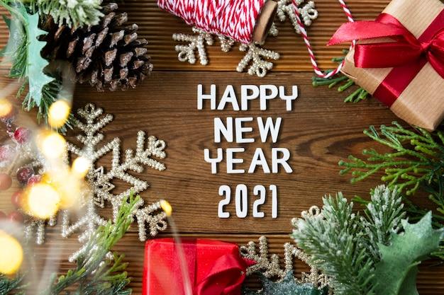 Gelukkig nieuwjaar 2021, rode geschenkdozen, dennentakken en kerstversiering op houten tafel.