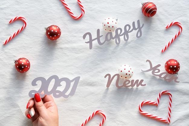 Gelukkig nieuwjaar 2021 tekst. kerstversiering - harten van zuurstokken, rood-witte snuisterijen op