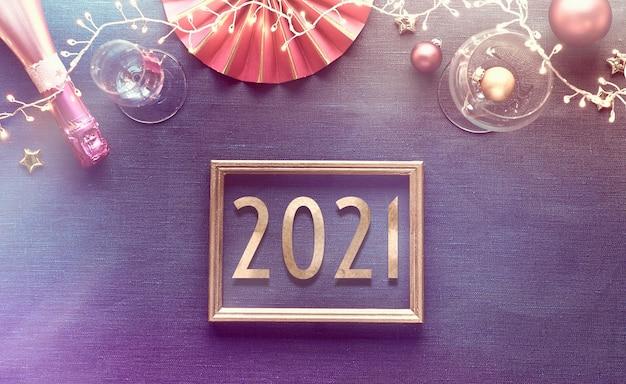 Gelukkig nieuwjaar 2021 vergulde tekst in frame met opstelling nieuwjaarsfeesttafel. plat lag in goud, roze en paars op linnen textiel.