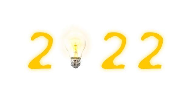 Gelukkig nieuwjaar 2022 geschreven met gloeiende gloeilamp en cijfers 2