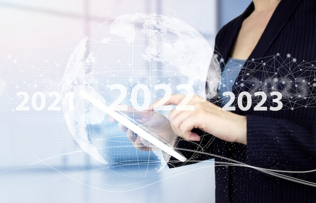 Gelukkig nieuwjaar 2022 - handaanraking witte tablet met digitaal hologram 2022 teken op lichte onscherpe achtergrond. concept voor visie 2021-2022. zakenman welkom jaar 2022.