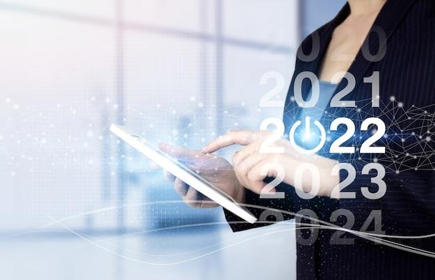 Gelukkig nieuwjaar 2022 - handaanraking witte tablet met digitaal hologram 2022 teken op lichte onscherpe achtergrond. nieuwjaar 2022, doel, plan, actie.