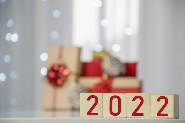 Gelukkig nieuwjaar 2022 op houten kubusblokken met geschenkdozen en wazig bokeh lichten op de achtergrond. wenskaart voor wintervakantie en kerstmis.