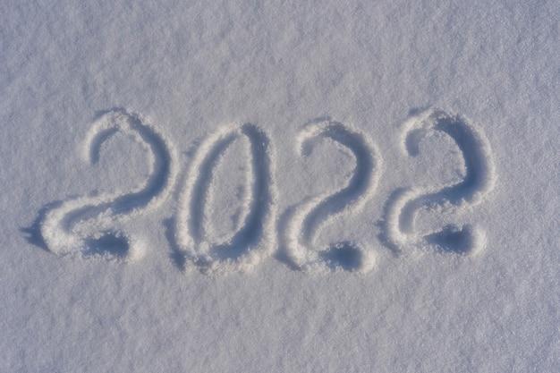Gelukkig nieuwjaar 2022 teken tekst geschreven met nummers van sneeuw op sneeuw oppervlak, symbool van het volgende jaar gemarkeerd tegen een besneeuwde winter achtergrond