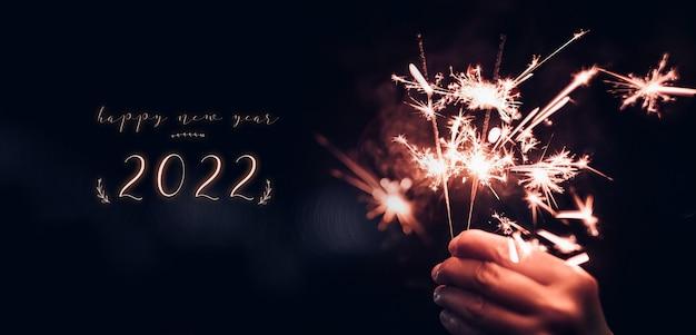 Gelukkig nieuwjaar 2022 tekst met hand met brandende sparkler vuurwerk ontploffing met op een zwarte bokeh achtergrond 's nachts, vakantie feest evenement partij, donkere vintage toon Premium Foto