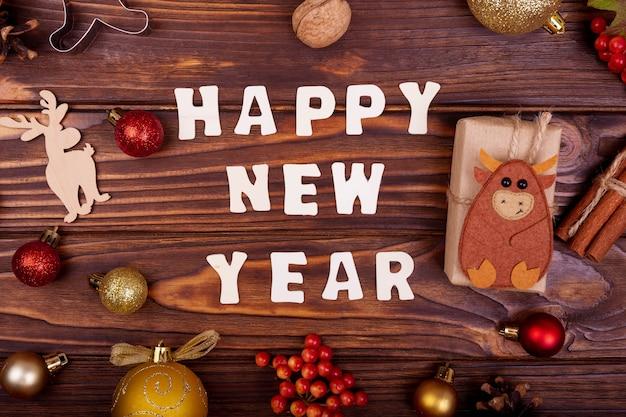 Gelukkig nieuwjaar ansichtkaart met wensen. kerstvakantie samenstelling met kerstboomversiering en geschenkdozen op donkere houten bord