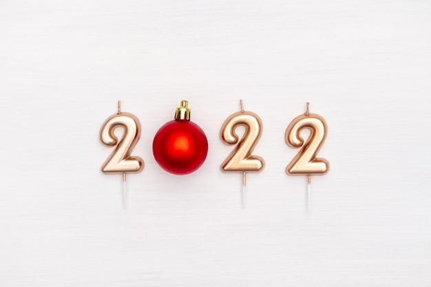 Gelukkig nieuwjaar en kerstviering feestelijke gouden nummer kaarsen kerst rode bal op wit